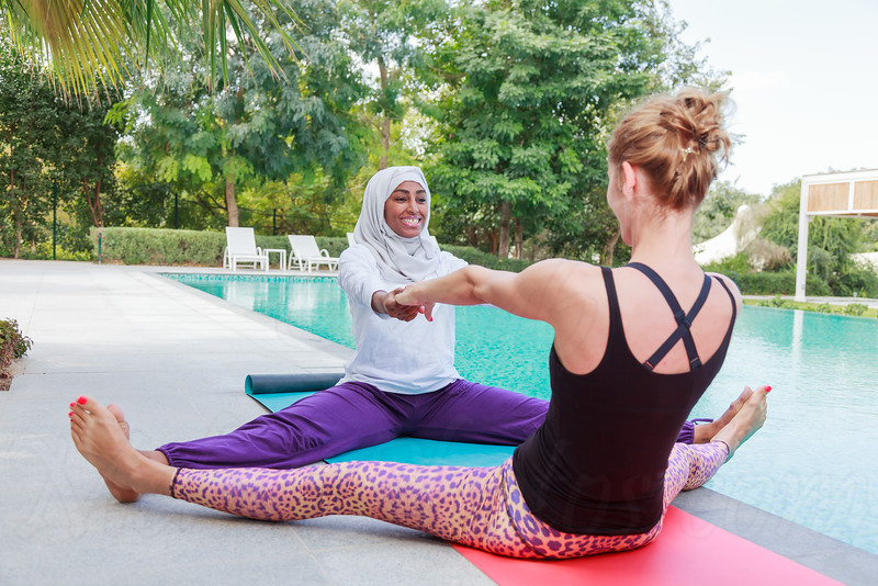 Two women practicing yoga outdoor in pair next to a swimming pool