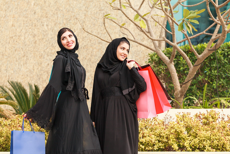 Two Emarati Arab women coming out of shopping with bags in her hand in Dubai, United Arab Emirates.
