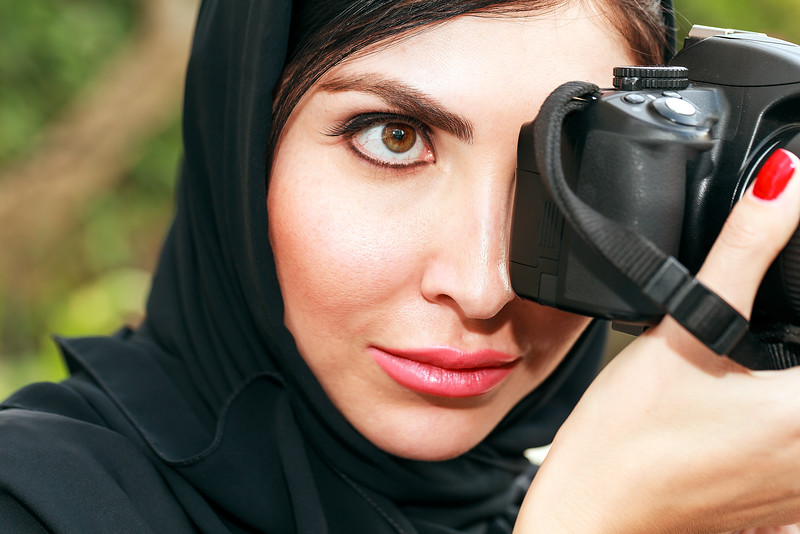 An Arab Business Women taking photo while looking through her professional Camera