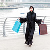 Emarati Arab woman coming out of shopping with bags in her hand in Dubai, United Arab Emirates.
