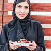 A white beautiful woman with abaya and hijab is standing with a bowl of date in hand.