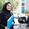 Two Arab Business Women Discussing next to a car, one inside and one standing out with a blue folder in hand.