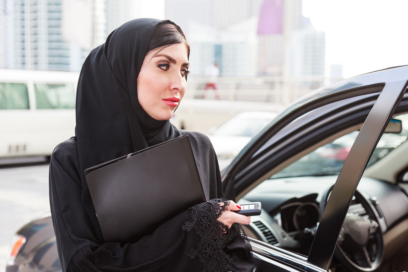 Emarati Arab Business woman opening her car door in Dubai, United Arab Emirates.