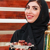 A white beautiful woman with abaya and hijab is standing with a bowl of date and a lantern in hand.