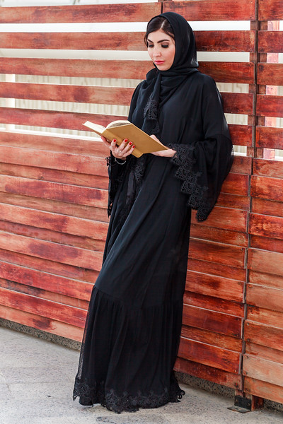 A white beautiful woman with abaya and hijab is standing reading a book in hand.