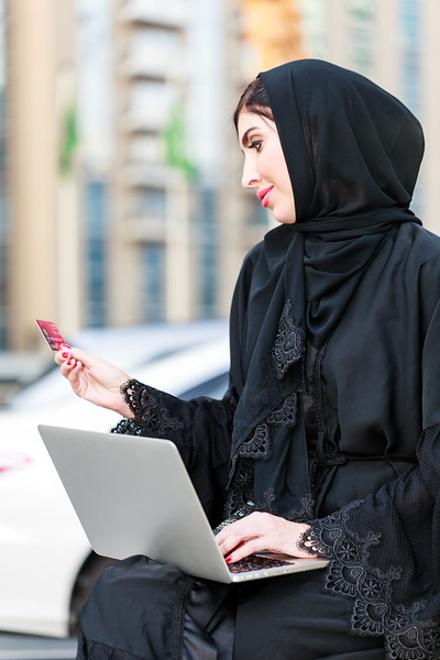 Emarati Arab Business woman outside the office working with her laptop while checking on her bank card in Dubai, United Arab Emirates.