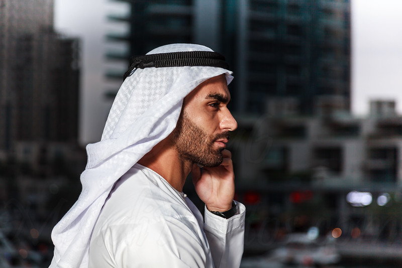 Young confident Emirati man standing by the canal talking on the phone in Dubai Marina.