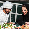 Arab couple looking at their mobile after dining in Dubai UAE.