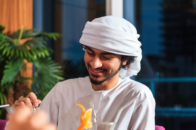 Young confident Emirati man sitting and eating in a restaurant in Dubai Marina.