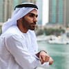 Young confident Emirati man standing by the canal in Dubai Marina.