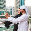 Young Emirati couple taking photos or selfie, Dubai, UAE.