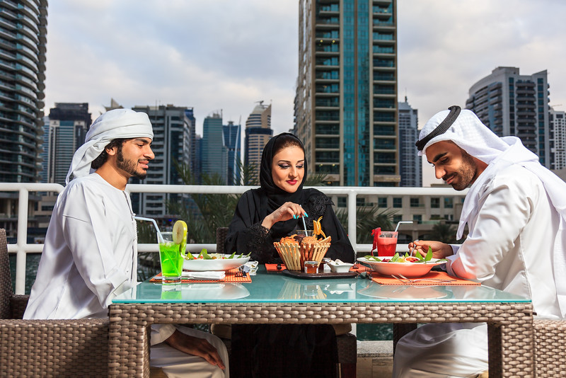 Arab couple looking at their mobile and discussing after dining in Dubai UAE.