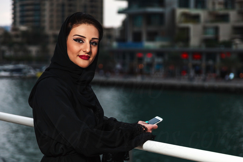 Young and beautiful Emirati woman standing next to canal in Dubai Marina.