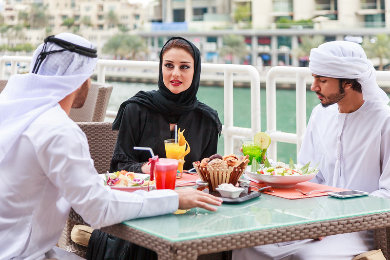 Arab couple talking at a restaurant while dining in Dubai UAE.
