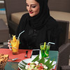 Young and beautiful Emirati woman sitting by the canal in Dubai Marina ready to order food.