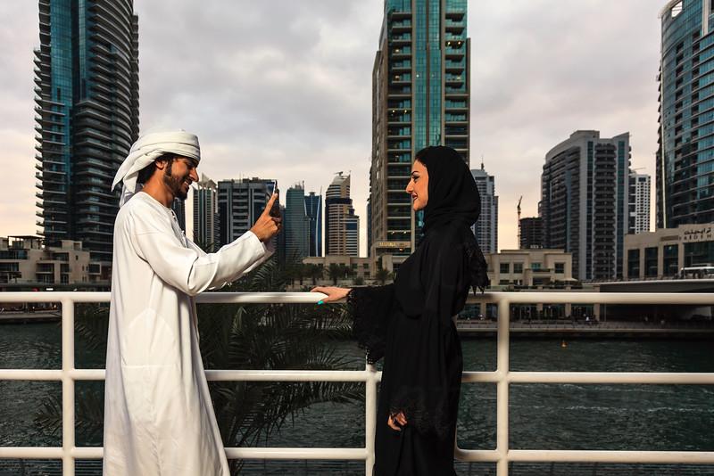 Young Emirati couple taking photos or selfie, Dubai, UAE.