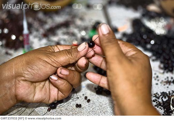 Close-up of a person's hands making beaded jewelry, Izamal, Yucatan, Mexico