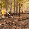 Record-Eagle/Douglas Tesner<br /> <br /> Lucas Merrick, a forester with the Michigan Department of Natural Resources, sprays down hot spots in a burned area near Golfview Road in Graying.