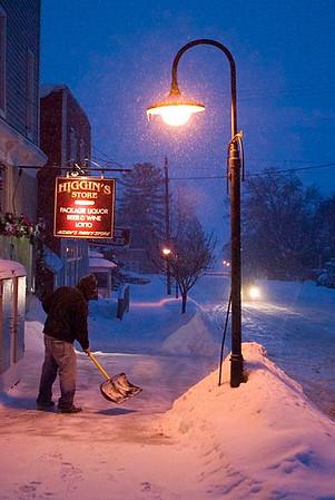 Record-Eagle/Jan-Michael Stump<br /> <br /> Blake Bartel shovels snow outside of Higgins Store on a snowy evening in Alden.
