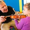 Record-Eagle/Douglas Tesner<br /> <br /> Tom Kaufmann provides words of encouragement to Sierra Batcha, 4, while she practices on a small violin at Tom Kaufmann's Instrument Petting Zoo held at the Great Lakes Children's Museum.  Kaufmann, also know, as Mr. Tinkertunes, has been  introducing young children to a wide range of instruments for over 14 years at a variety of venues.