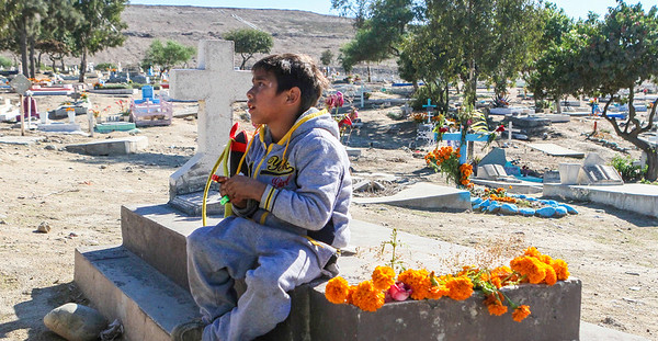"""John Chaides<br /> A child sits atop a grave across the street from the """"El Dumpe"""" Clinic by Healing Hearts Across Borders in Tijuana, Mexico on Saturday, November 11, 2017. """"El Dumpe"""" is on the site of a former landfill and life expectancy in the past was once low but since has risen."""