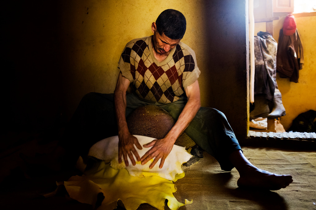 A worker hand-dyes hides yellow with saffron inside the Chouara tannery in the Medina in Fes, Morocco.