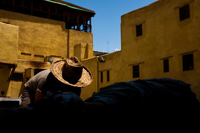 A worker removes hides from a white liquid where they were softened before they can be dyed at the Chouara tannery in the Medina in Fes, Morocco.