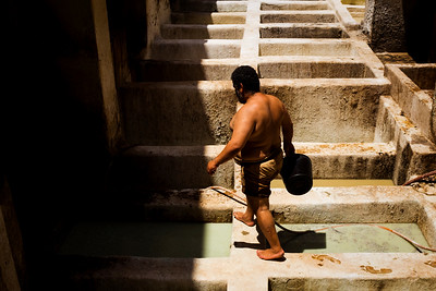 A worker carries vats of liquid between wells at the Chouara tannery in the Medina in Fes, Morocco.