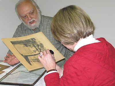 Record-Eagle/Lisa Perkins<br /> Appraiser Don Butkovich instructs Martha Scarborough in what to look for in determining that her JM Whistler etching is a reproduction during an appraisal day Saturday at the Dennos Museum Center.