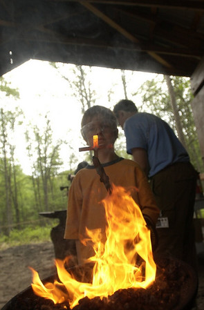 Record-Eagle/Garret Leiva<br /> Kenny Zak, 11, a Boy Scout with Troop 27 in Traverse City, pulls his handiwork out of the forge in the Outdoors Skills Area at Camp Greilick. Along with blacksmithing skills, Scouts can earned merit badges in wilderness survival, camping, hiking, backpacking and orienteering.