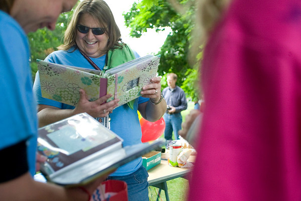 Record-Eagle/Jan-Michael Stump<br /> Fifth-grade teachers Renee Kolle, left, and Karen Nelson look through books their Easter Elementary School students made for them as gifts during a class picnic outside on the last day of school.