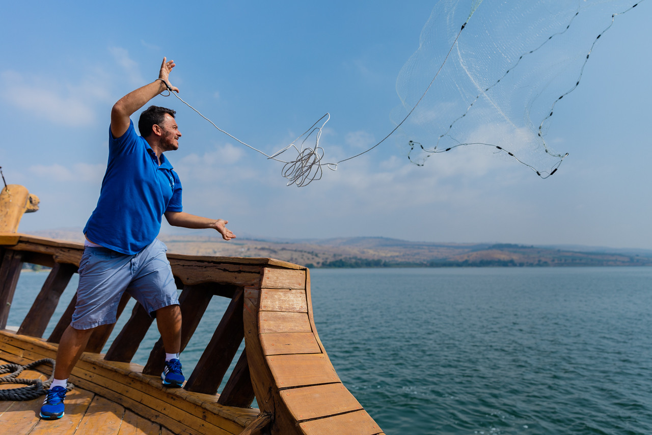 Boatman casts his net to catch St. Peter's fish