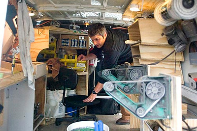 """Record-Eagle/Jan-Michael Stump<br /> Tony Valerio works in the back of his specially outfitted van parked on a street in Petoskey. """"Its my mobile lemonade stand, but no one has the type of lemonade I have,"""" he said."""