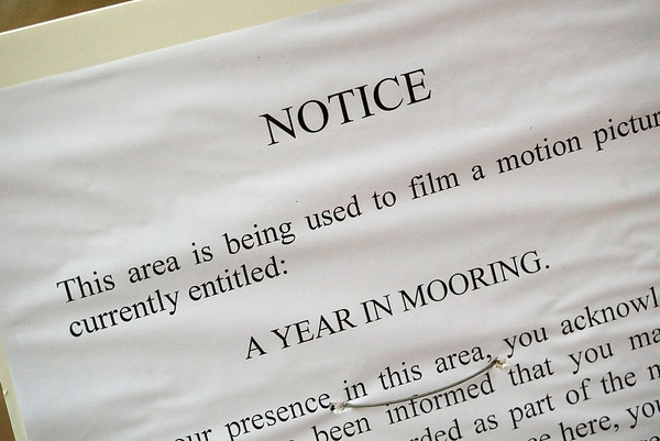 """Record-Eagle/Jan-Michael Stump<br /> A poster gives notice to pedestrians on East Front Street of the filming of a scene for """"A Year in Mooring,"""" an independent film being shot in Traverse City."""