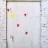 Record-Eagle/Vanessa McCray<br /> A cluster of red hearts with one lone yellow heart dot a building wall located off Union Street in downtown Traverse City.