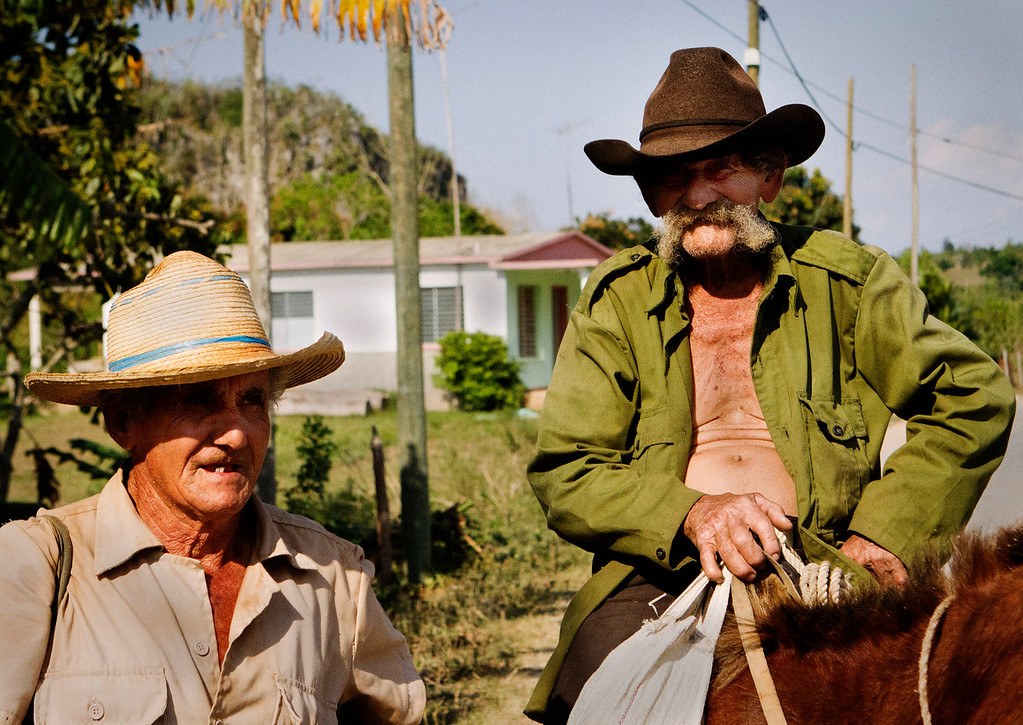 Two men stop to talk on the side of a road outside of Viñales, Cuba.