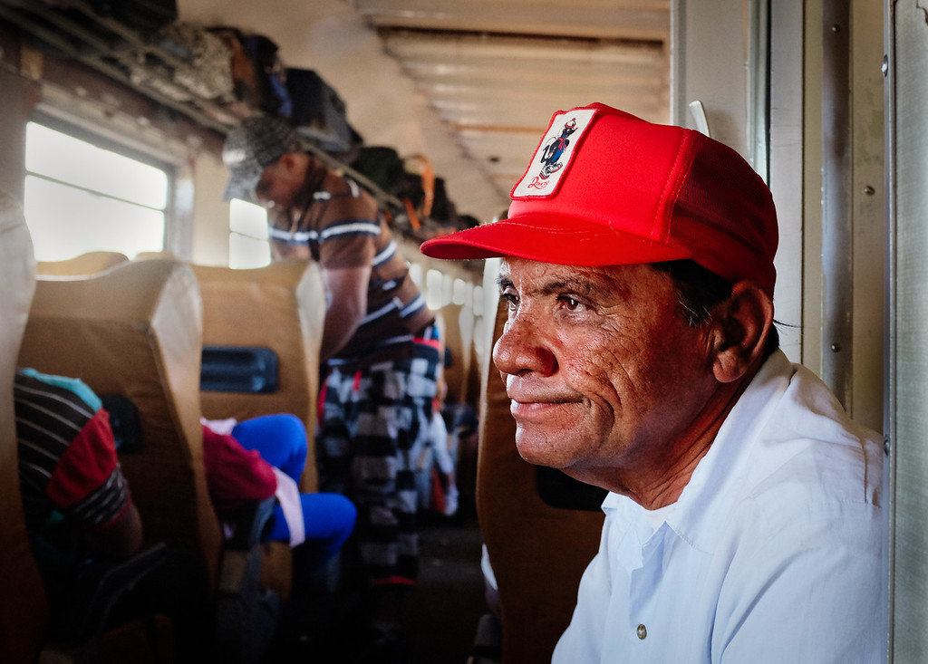 A man sits and smokes in between train cars during the journey to Santiago de Cuba.