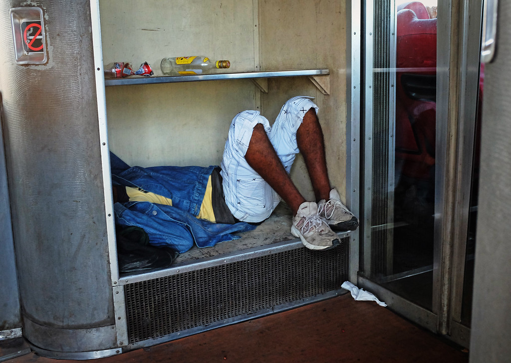 A man takes a nap in between train cars following a night of drinking as the train approaches San Luis, Cuba during the ride from Havana to Santiago de Cuba.