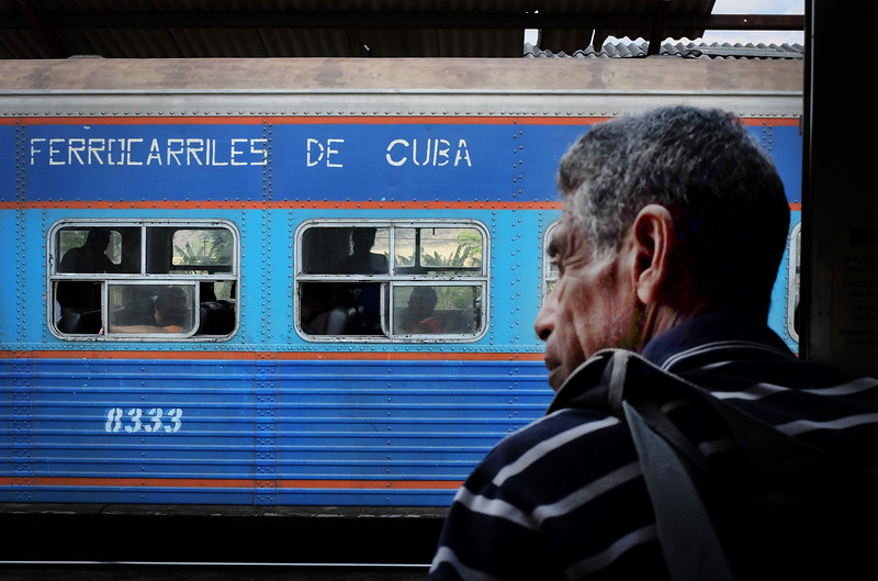 A man looks out of the railway car at a passing train that is heading west towards Havana near San Luis, Cuba. Cuba was the 6th nation in the world to have a train system.