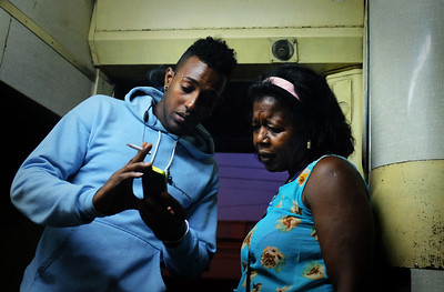 A young man shows a woman photos of his girlfriend on his phone as they smoke in the train near Camagüey, Cuba during the ride from Havana to Santiago de Cuba.