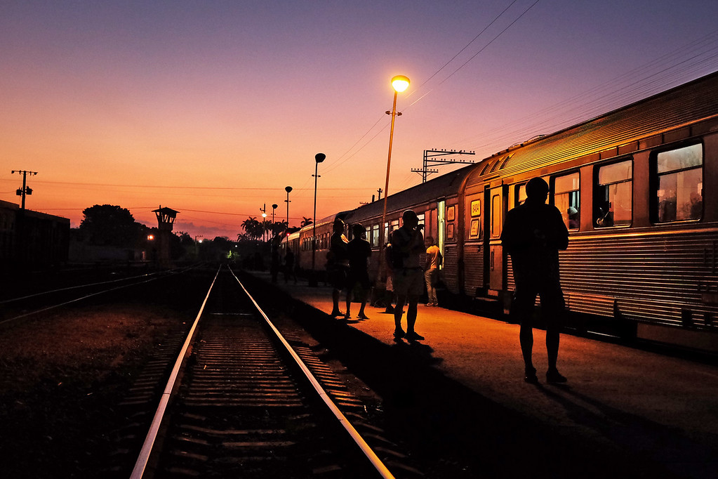 People get out of the train to talk and smoke while the train stops in Camaguey, Cuba in the early morning.