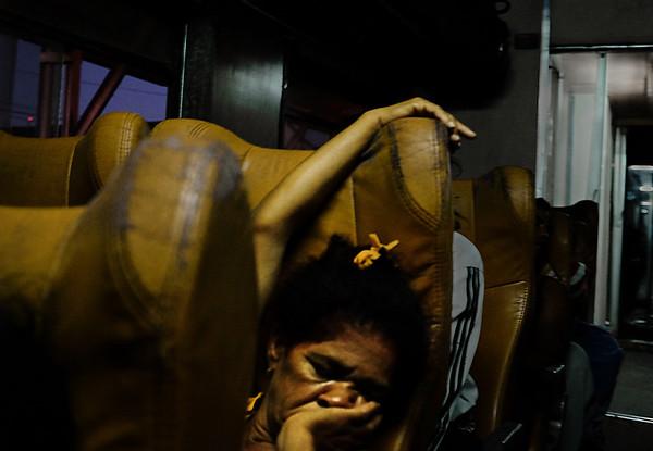 A grandmother takes a quick nap when her grandson finally falls asleep on the train ride from Havana to Santiago de Cuba as the sun rises near Camagüey, Cuba.