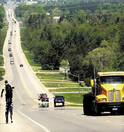 Record-Eagle/Tyler Sipe<br /> Neil Sauter waves to a honking motorist as he walks on 3-feet-tall stilts along the shoulder of M-37 near Grawn. Sauter was walking to raise funds for cerebral palsy.
