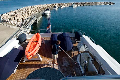 Record-Eagle/Jan-Michael Stump<br /> Mate James Southgate scrubs the deck of the CV-9. The ship carries three jet skis, two kayaks and two tenders among its recreational equipment. The crew of eight works year-round on the ship to keep it seaworthy.