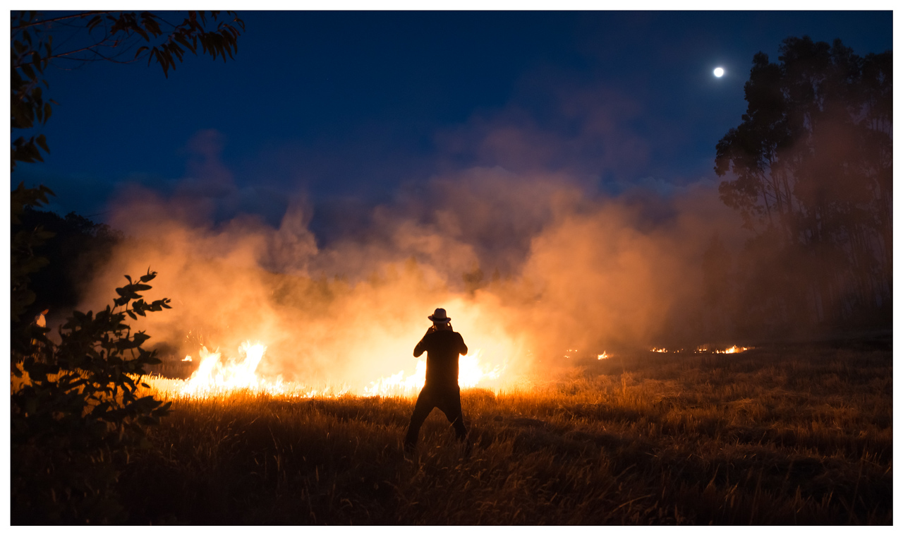 A man photographs a burning field in the Andes, Ecuador.