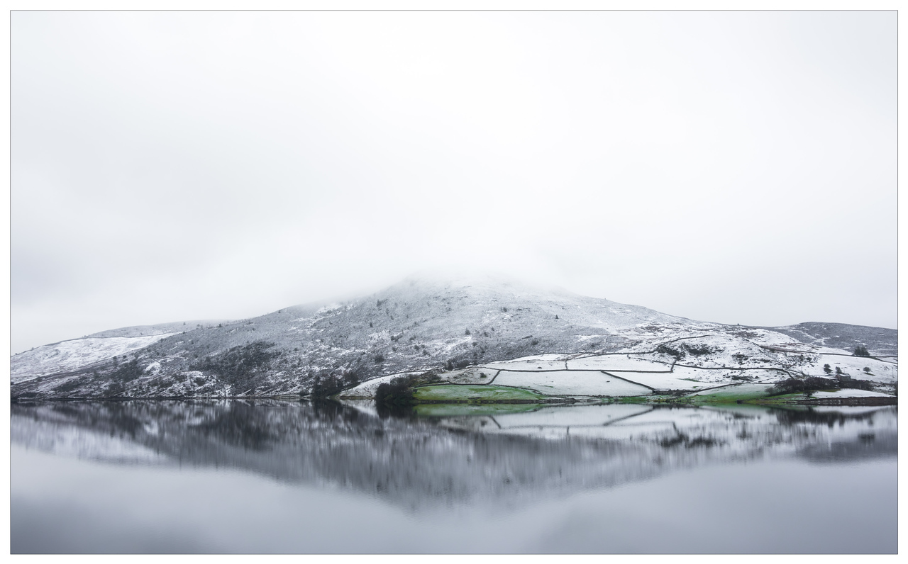 A snowy mountain in Snowdonia reflected in a lake.
