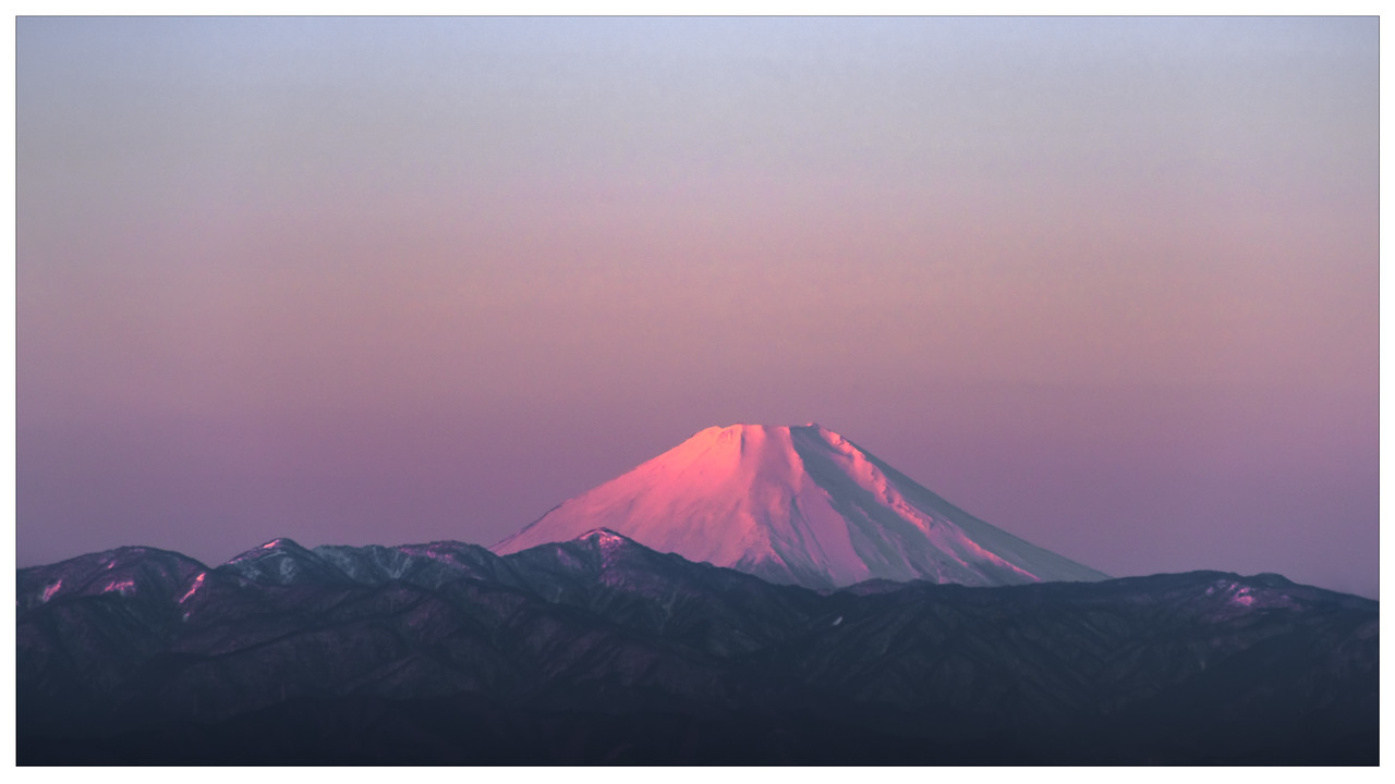 A glorious purple hued sunrise over Mount Fuji and the surrounding landscape near Tokyo, Japan.