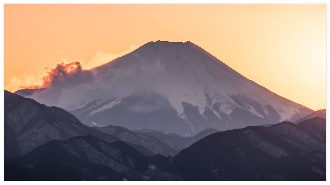 Mount Fuji with the sun setting behind it, as seen from Mount Takao in Tokyo, Japan.