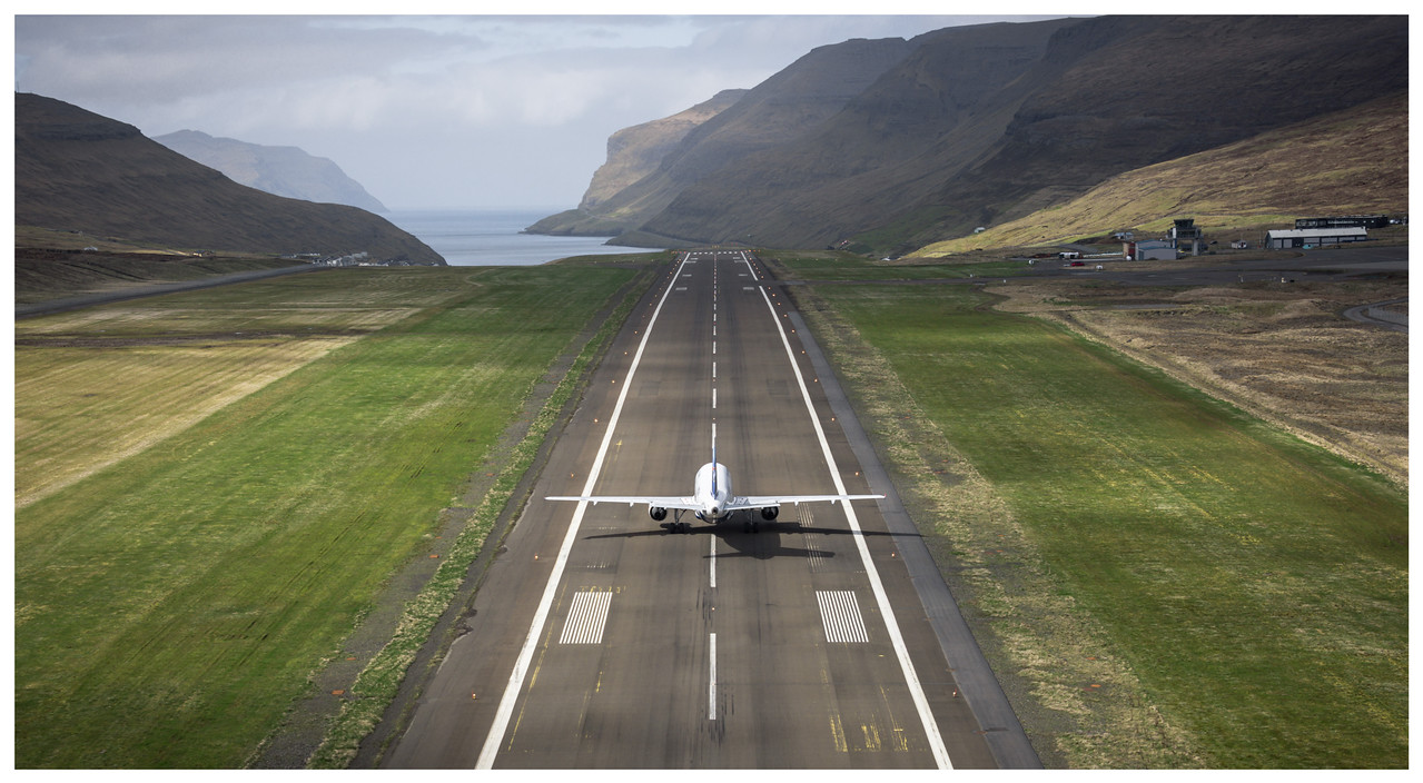 A high, rear, view behind a plane as it's about to take off down the runway.