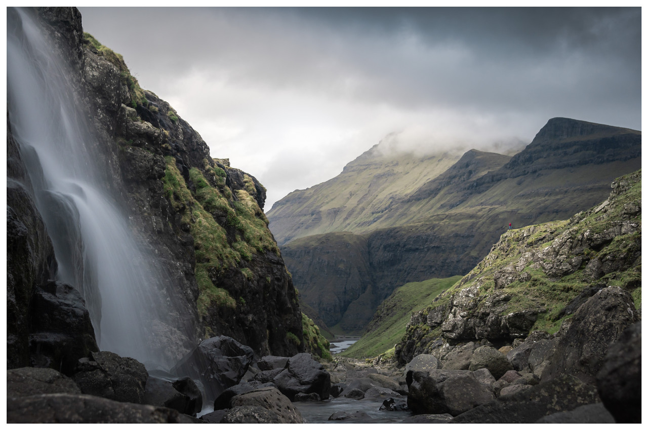 A waterfall in the foreground with mountains in the background.
